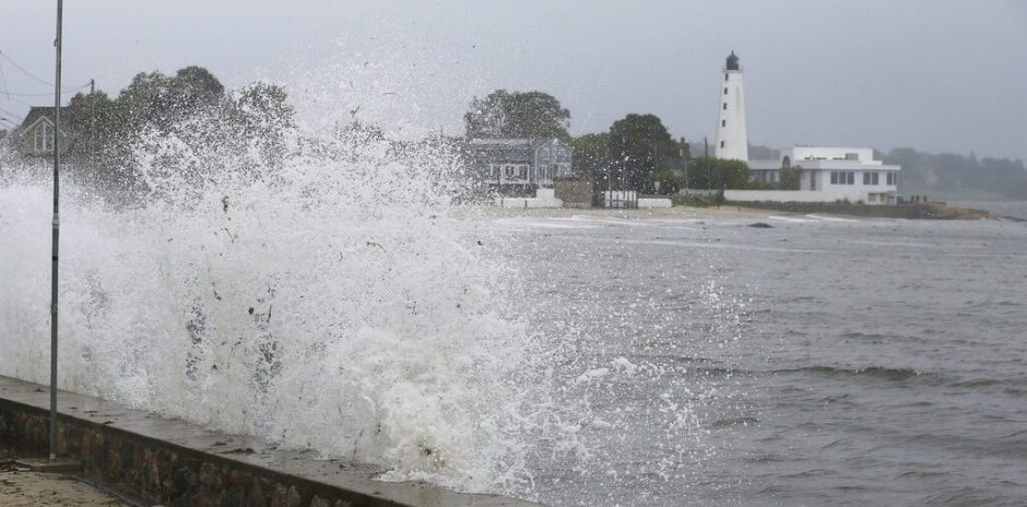 Waves crash against the sea wall near New London Harbor Lighthouse Sunday.