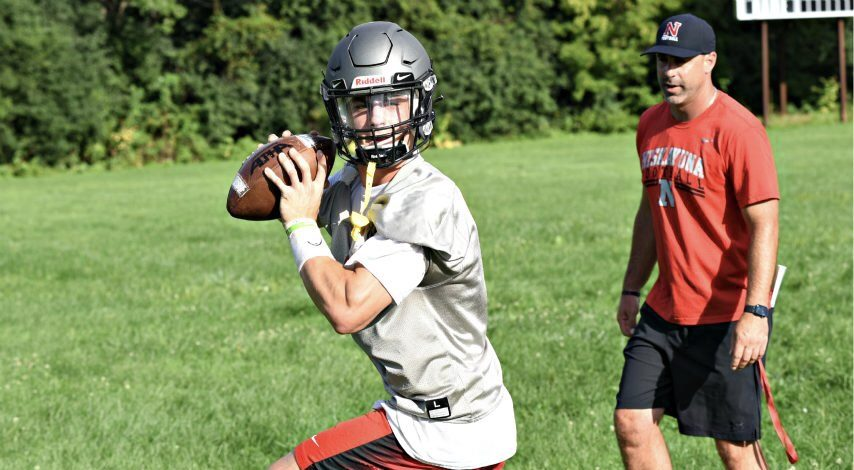 Niskayuna High School senior Dan Quinn drops back to throw a pass during practice as coach Brian Grastorf watches Monday afternoon.