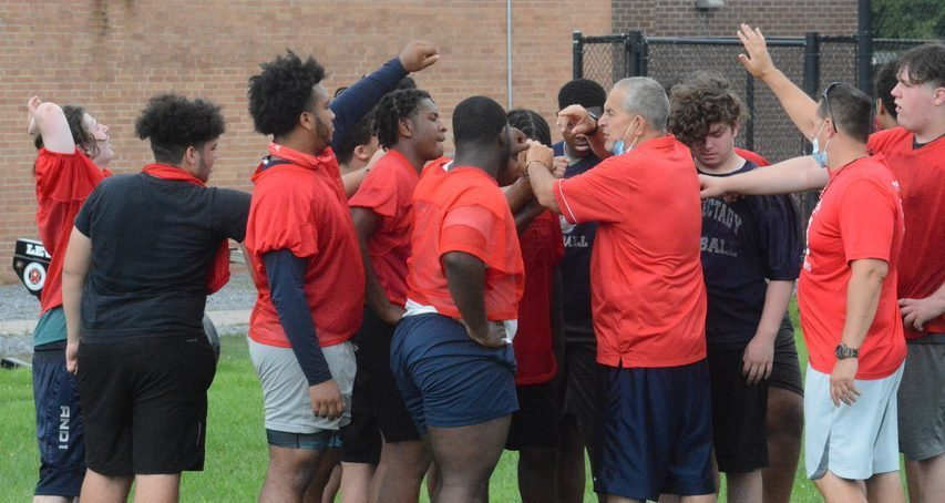 Schenectady football coach Carm DePoalo huddles with players during practice on Tuesday, Aug. 24 at Schenectady High School.