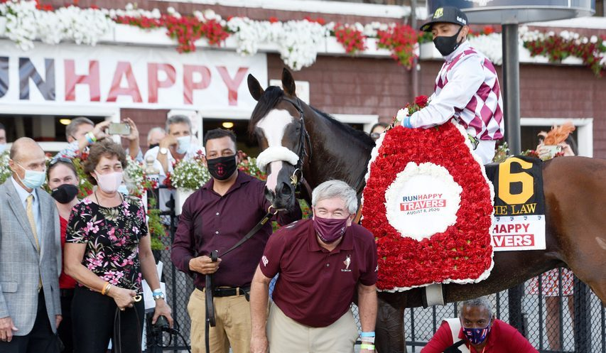 Tiz the Law, with jockey Manny Franco aboard, gives Sackatoga Stable operating manager Jack Knowlton a small nibble in the winner's circle after Tiz the Law won the 151st Travers Stakes on Aug. 8, 2020 at Saratoga Race Course.