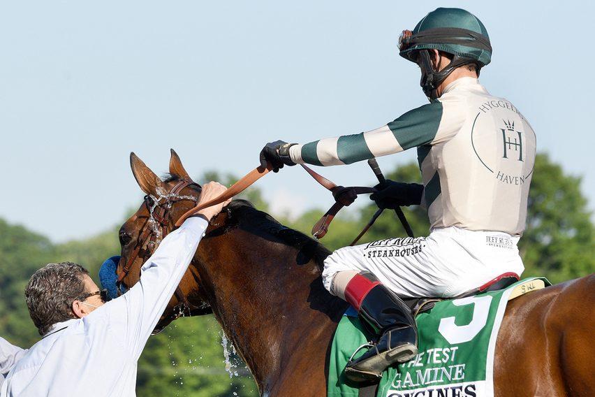 Jockey John Velazquez gives assistant trainer Jimmy Barnes a fist bump after Gamine won the 2020 Test at Saratoga.