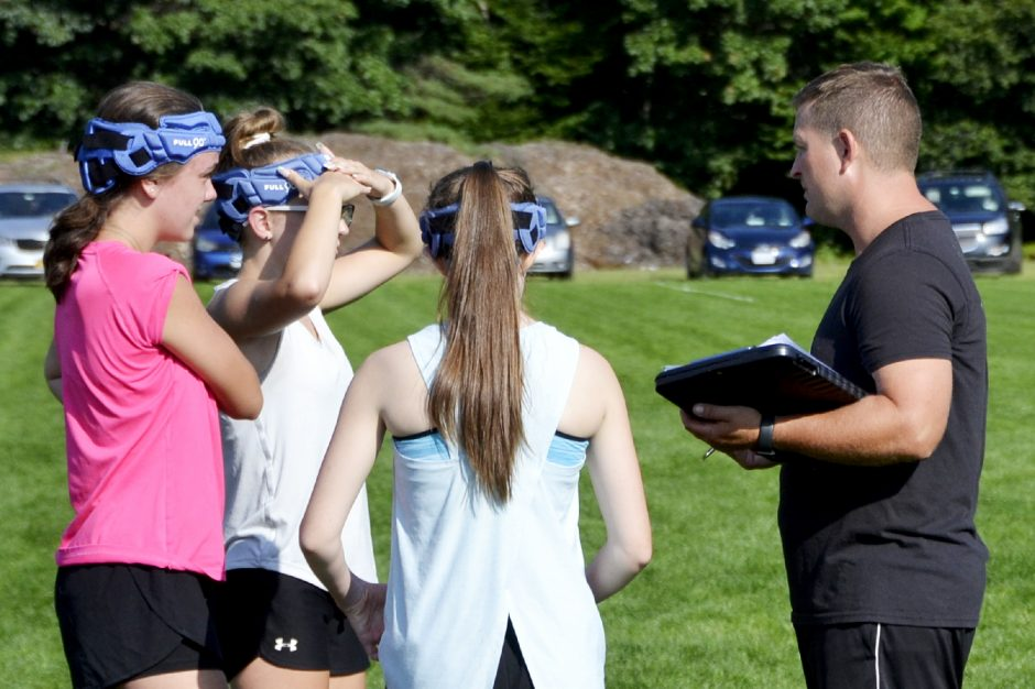 Northville High School girls' soccer coach Doug Hammons, right, talks to some of his players during practice at the Prospect Street Fields in Northville on Wednesday.