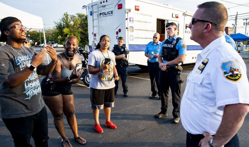 Protesters yell at Schenectady Police Chief Eric Clifford at a law enforcement and Schenectady Fire Department community outreach event at State and Albany streets Thursday.