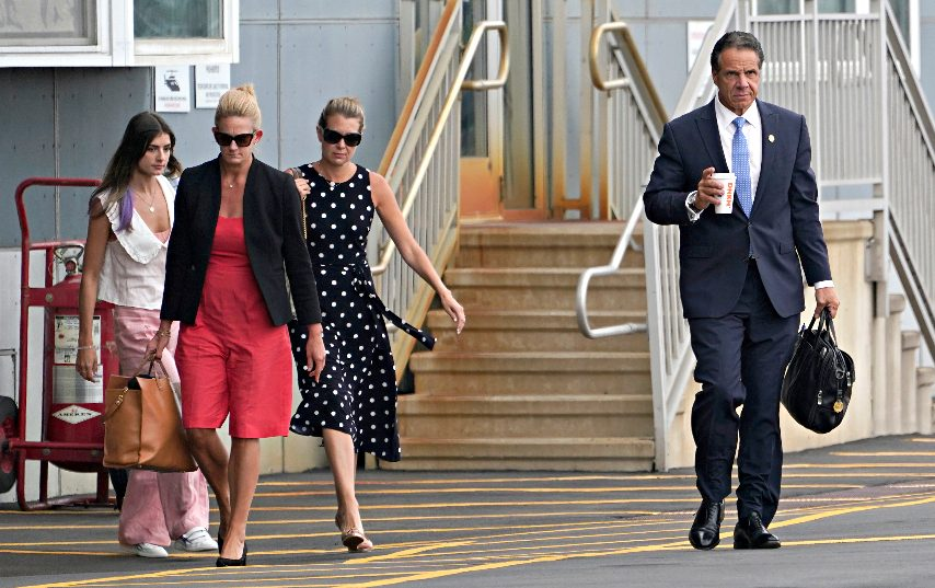 Andrew Cuomo, right, is followed by his daughter Michaela Kennedy Cuomo, from left, Office Director Stephanie Benton and former Executive Secretary Melissa DeRosa as they prepare to board a helicopter after announcing Cuomo's resignation, Tuesday, Aug. 10, 2021, in New York. (Seth Wenig/The Associated Press)