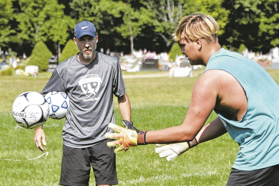 Northville boys' varsity soccer coach Steve Clapper, left, watches Dan VanNostrand in a goalie drill during practice Wednesday at the Prospect Street Fields in Northville.