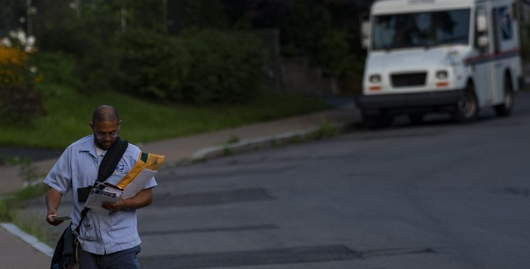A postal worker delivers mail in the gathering dusk on White Street in Schenectady around 7 p.m. onAug. 27.