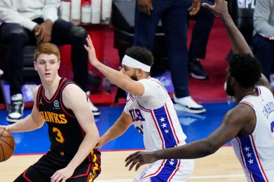 The Atlanta Hawks' Kevin Huerter, left, tries to get past Philadelphia 76ers' Seth Curry, center, and Joel Embiid during the second half of Game 7 in a second-round NBA basketball playoff series, Sunday, June 20, 2021, in Philadelphia. (Matt Slocum/The Associated Press)