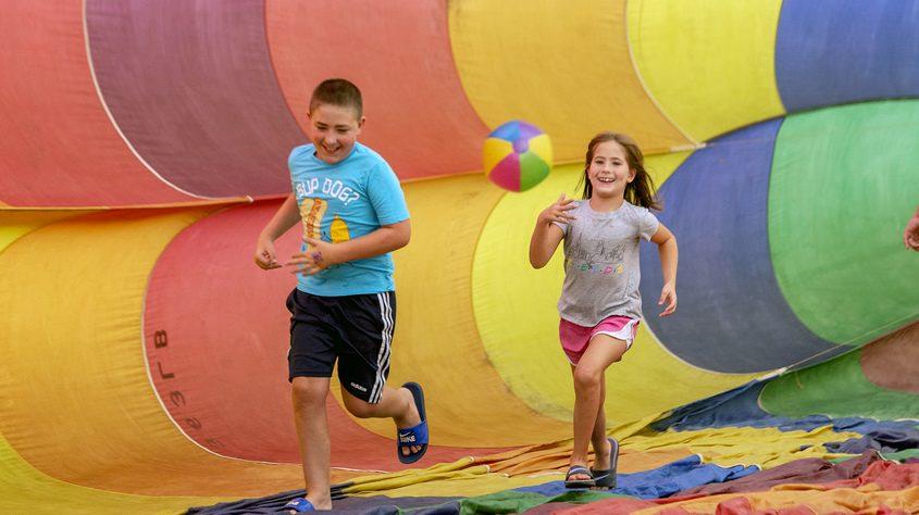 Evan Sartori, 11, and sister Cecelia, 6, run around inside a balloon from Adirondack Balloon Flights. Sunday.