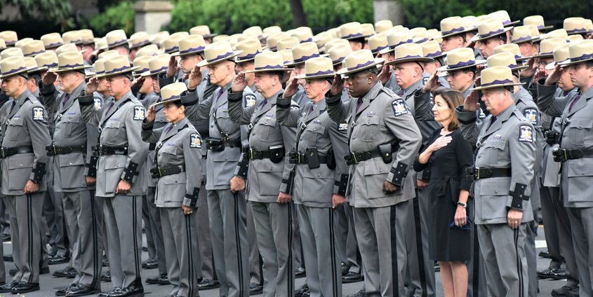 Governor Kathy Hochul stands with New York State Troopers and other law enforcement officers prior to the funeral service for fallen trooper James J. Monda