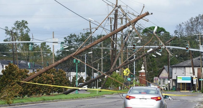 Traffic diverts around downed power lines Monday in Metairie, La.