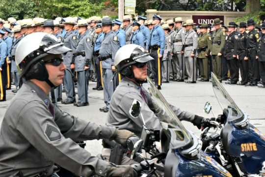 Troopers and other law enforcement officers stand at the end of the funeral service for fallen trooper James J. Monda