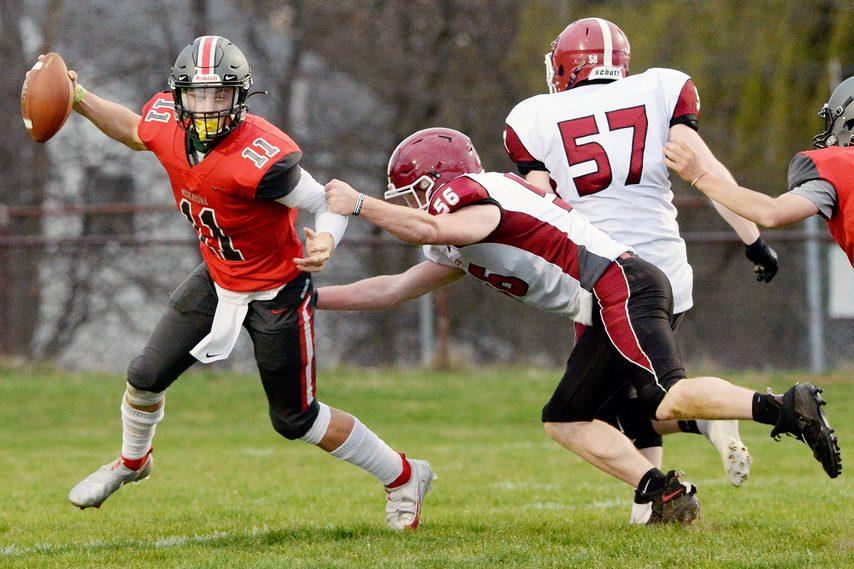 Niskayuna's Dan Quinn, left, runs with the ball during a high school football game at Niskayuna High School on Friday, April 9, 2021.