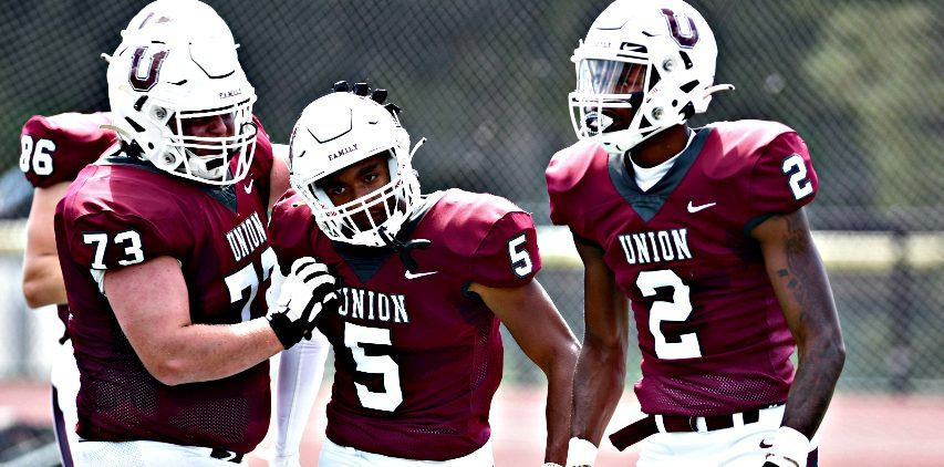 Robbie Tolbert, center, celebrates after scoring a touchdown in Saturday's Union football win in Schenectady.