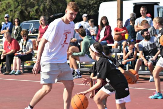 A young basketball player looks to drive past Shenendehowa grad and current Atlanta Hawk Kevin Huerter Saturday morning at the Clifton Common outdoor basketball courts in Clifton Park.