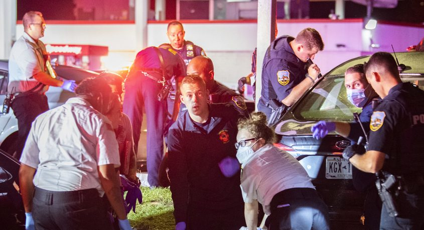 A Mohawk Ambulance EMT performs CPR on a gun shot victim in the parking lot of the Tropics on Brandywine Avenueearly Sunday