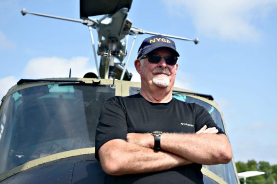Michael Collins, 75, stands in front of a U.S. Army UH-1M or Huey 1 at the Schenectady County Airport.