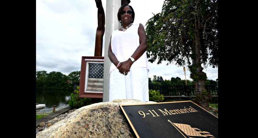 Diane Sanders Hombach stands beside the 9/11 memorial at Waters Edge Lighthouse in Glenville.