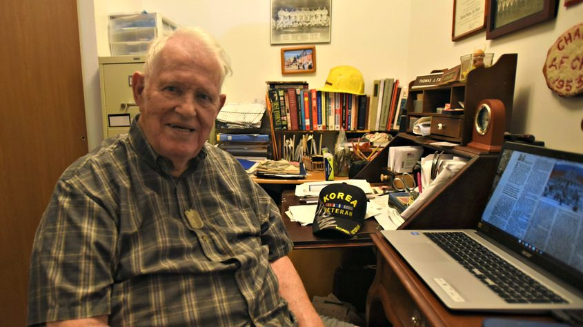 90-year-old Tom Farnan sits at a desk in his home office in Johnstown
