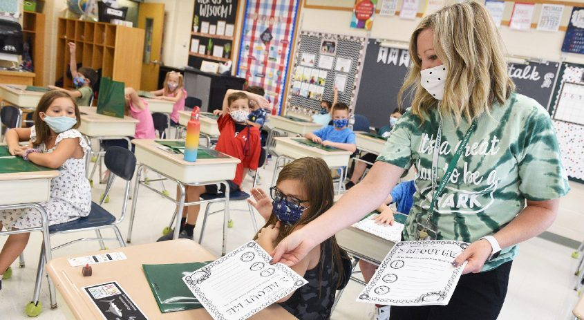 Third-grade teacher Molly Brown hands out worksheets to her students during the first day of class at Shatekon Elementary School in Clifton Park on Wednesday.