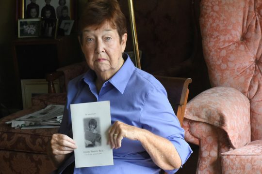 """Margaret """"Midge"""" Launsbach holds the program from her cousin Eileen Keegan Rice's services in her home. Her cousin died in the 9/11 attacks."""