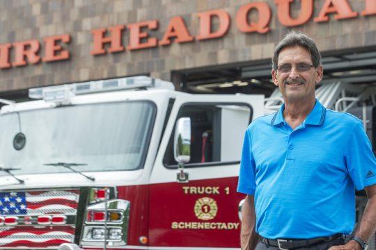Retired Schenectady Fire Dept. Captain Richard Nebolini stands outside SFD Engine Truck 1 in Schenectady.