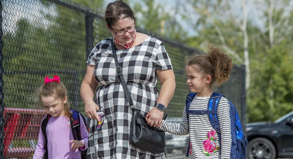 Erin Henry walks her daughters Isabel Vargas, 5, left, and Rosalie Vargas, 8, home after their first day of classes at Marie Curie Institute in Amsterdam on Wednesday.
