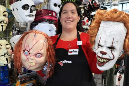 Sales Manager Elizabeth Kulkus poses with Chucky and Pennywise masks at The Costumer's new Mohawk Harbor retail shop Thursday, Sept. 9, 2021.