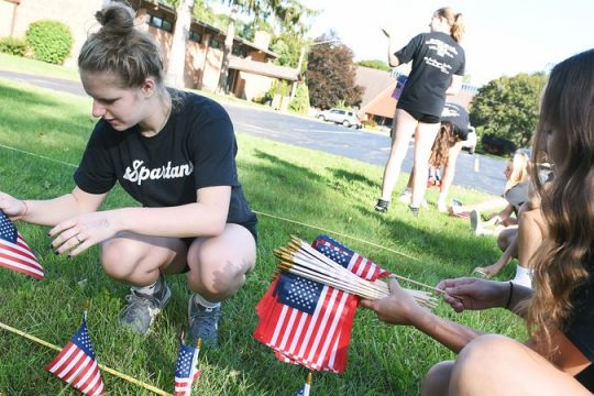 Burnt Hills girls' volleyball players Sophia Goss, left, and Jenna Vaughan place plant American flags in tribute to 9/11 at the Church of the Immaculate Conception Church in Glenville on Friday.