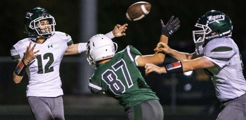 Hudson Falls quarterback Will Coon is pressured by Schalmont's Ryan Woodrow during Friday's high school football game at Schalmont High School.