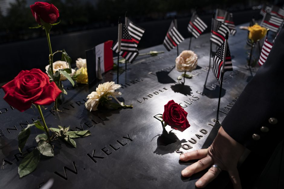 A firefighter places his hand on the name engravings on the south pool during ceremonies to commemorate the 20th anniversary of the Sept. 11 terrorist attacks, Saturday, Sept. 11, 2021, at the National September 11 Memorial & Museum in New York. (John Minchillo/The Associated Press)