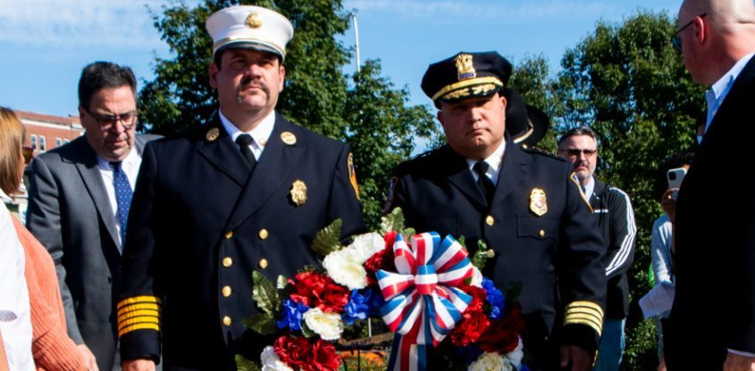 Amsterdam Fire Chief Anthony Agresta, left, and Amsterdam Police Chief John Thomas lay a wreath during a ceremony in front of the 9/11 Memorial at Riverlink Park Saturday.