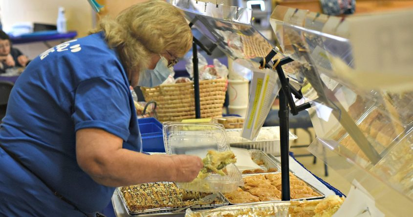 STAN HUDY/THE DAILY GAZETTE Maria Dostis of Rexford adds more galactobureko - semolina custard in filo - to a container Friday afternoon during the 45th annual St. George Greek Festival at the Hellenic Center 510 Liberty Street in Schenectady. Sept. 10, 2021.