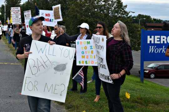 Rally organizer Jessica Blake of Amsterdam walks down the line of assembled protesters on Route 30 in Amsterdam Sept. 5 across from St. Mary's Healthcare because the organization will require proof of a COVID-19 vaccine by its employees by Oct. 1.