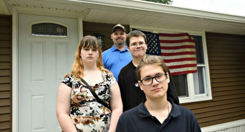 Jeremy Tobin, top, stands with several of his children, Ravyn, left middle, Phoenix and Cailean, front, outside their newly reconstructed home on Lakeside Avenue in Malta Gardens in Malta Sunday. The project was part of the Malta Veterans Appreciation Program (MVAP).