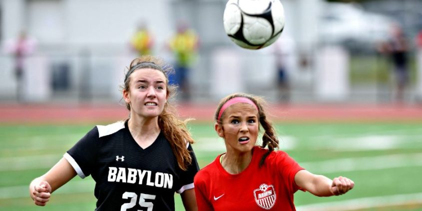 Mechanicville's Maddie Hopeck (14) fights for position with a Babylon defender on a ball in the air during a non-league girls' soccer contest Sunday afternoon at Mechanicville High School on the final day of the NYSSCOGS Hall of Fame Tournament.