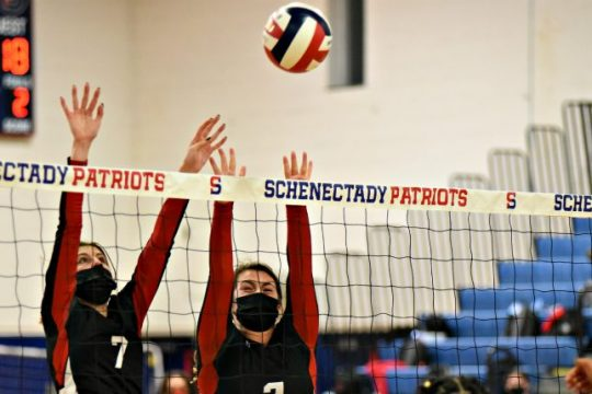 Guilderland's Lauren Hoyle (7) and Lauren Kinley (2) jump in an attempt to block Veverlyn Marrero Martinez's hit Tuesday afternoon at Schenectady High School.