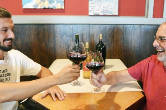 Lorenzo's Southside owner Joe Lanzi, right, cheers with his son Gaetano at their restaurant in Amsterdam on Monday. The inaugural wine competition will be held this weekend during the city's Italian Festival.
