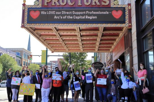 ARC staff and clients pose beneath a supportive message on the Proctors marquee on Thursday, Sep. 16, 2021.