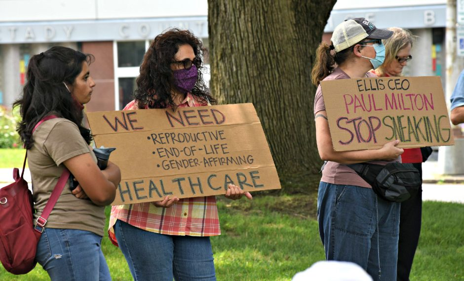 Aliya Saeed of Niskayuna, left and Holly Loth of Schenectady hold up signs during the SOS - Save our Services Rally (Ellis Medicine - Trinity Health Merger) held by the Schenectady Coalition for Healthcare Accessthe morning of Sunday, July 25, 2021, at Veteran's Park in Schenectady.
