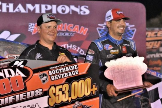 Fonda Speedway promoter Brett Deyo, left, presents Stewart Friesen with the winner's check and trophy during Victory Lane ceremonies following Friesen's second-straight win in the Fonda 200 presented by Southend Beverages Saturday at Fonda Speedway. (James A. Ellis/For The Daily Gazette)