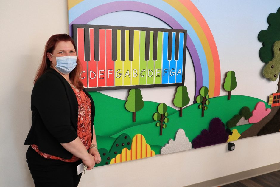 Practice administrator Christina Moran on Tuesday, June 8, 2021, stands beside a tactile sensory wall (with working piano keyboard) at Ellis Medicine's new and expanded child, adolescent and family mental health center in Schenectady.