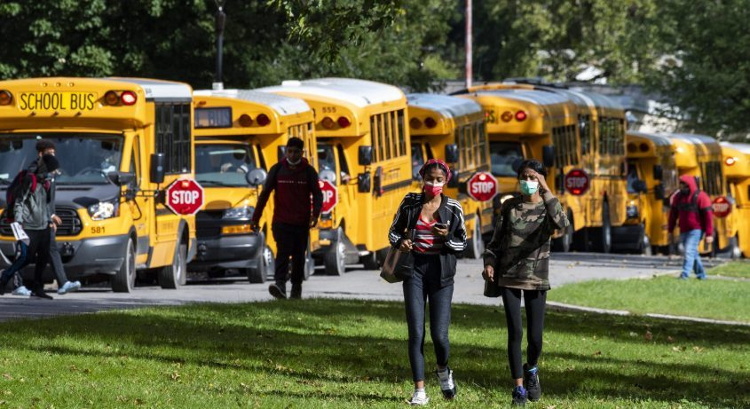 Schenectady High School students walk across the lawn in front of parked school busses at dismissal Tuesday.