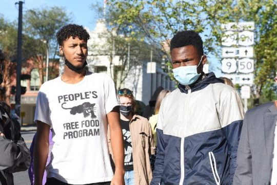 Activists, from left, Adam Walker of Troy, T.J. Sangare ofClifton Park and Andre Simmons of Schenectady, wait to make their way into the Saratoga Springs Police Department on Tuesday as they turn themselves inon charges stemming from a protest on July 14 in Saratoga Springs.