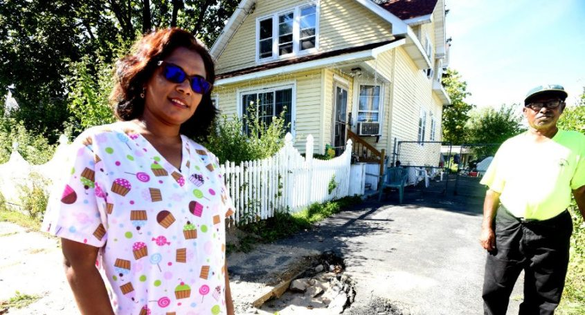 Gangadai Surooj stands in front of her two-family house on Edwards Street in Schenectady with her father, Mohipaul Bano.