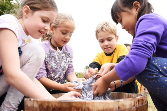In this October 2019 photo, Malta Ave Elementary students (L-R) Mollie Campanin, Ava Macri, Brandon Schlitzer, and Chloe Tong, all 7 at the time, learn about being a 'camp follower' as they wash clothing, learning about the Revolutionary War during Malta Ave Elementary School's Living History Encampment Day at Eastern Ave Recreation Field in Ballston Spa.
