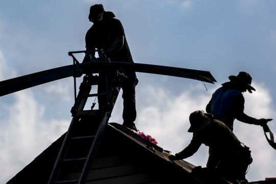 Roofers work high above Helderberg Avenue in Schenectady replacing shingles and flashing in this file photo.