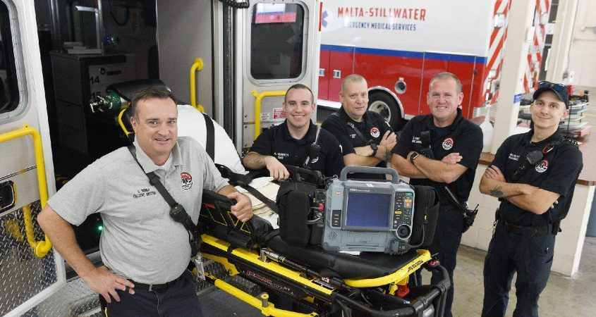 Malta-Stillwater EMS Executive Director Scott Skinner stands in front ofa stretcher with the day shift in back. Pictured, from left,are EMT Alex Manios, paramedic supervisor Kevin Robert, EMT Jeremy Swint and paramedic Glen Blakley at their station in Malta on Wednesday.