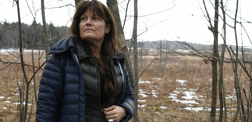 Lynne Bruning of Duanesburg stands on her property line in December 2019. A solar array is proposed to be installed just behind her.