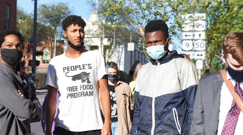 Activists, from left, Adam Walker, T.J. Sangare and Andre Simmons on Tuesday make their way into Saratoga Springs Police Departmentto turn themselves inon chargesstemming from a protest on July 14 in Saratoga Springs. Supporters of those who had been arrested were prevented from entering court on Tuesday.