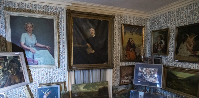 Some of the near 800 paintings in the collection from the late Paul Verbitsky that will go up for sale cover the walls of his home at 30 Lydius Street in Fort Plain on Thursday.